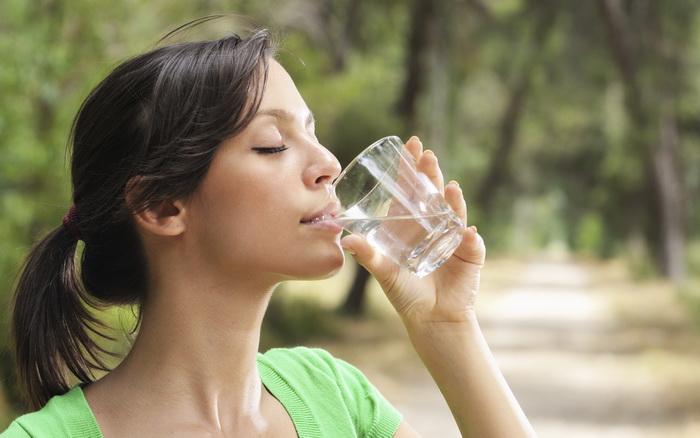 Молодая женщина пьет воду